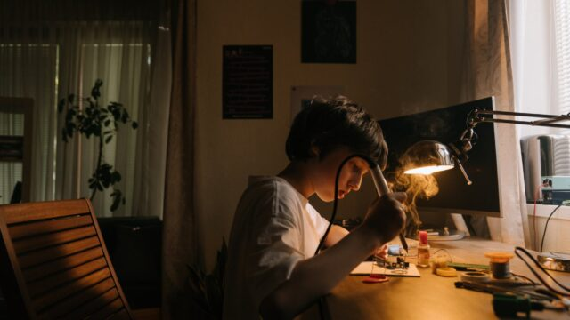 A child holds a soldering iron while looking at a soldering project. The smoke from soldering is visible in the bright light from a lamp on the work surface. Various electronics tools are scattered around the work surface.